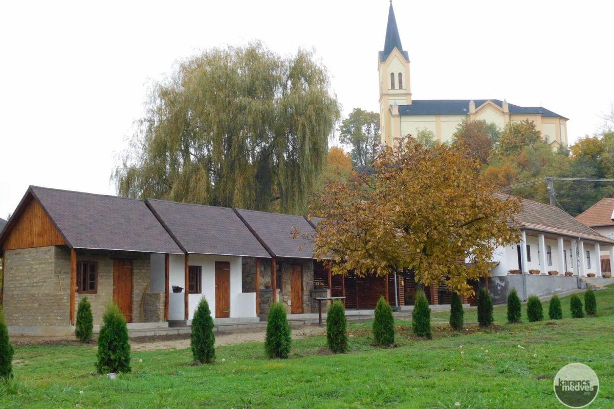 Kiemelt fotó: A Karancslapujtői Tájház, mögötte a község római katolikus temploma (karancs-medves.info fotó: Karancslapujtői Tájház)